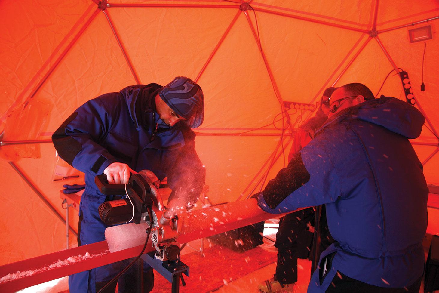 Patrick Ginot coupe la carotte de glace fraîchement prélevée, avant de la conditionner.