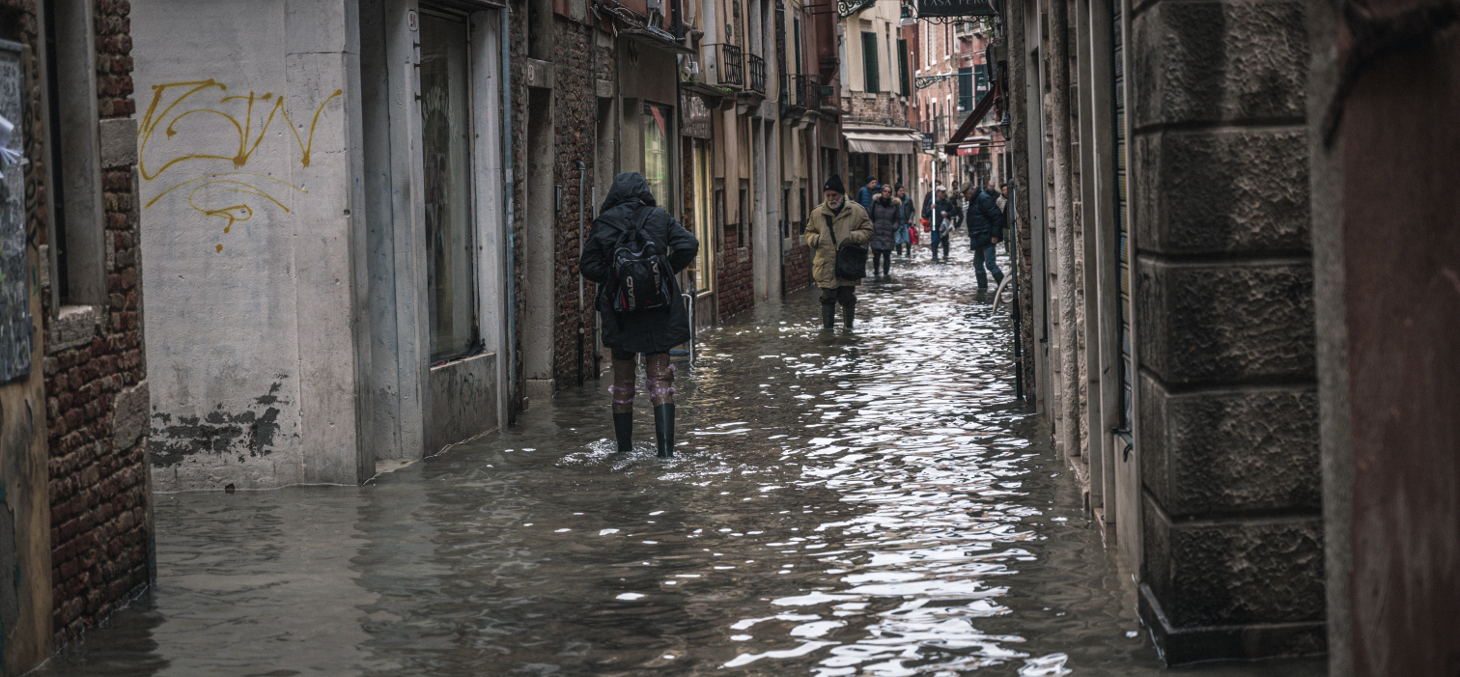 Venice, november 2019, locals and tourists endure the worst flood in more than 50 years in Venice lagoon. People pass the flooded streets of the city. Shutterstock